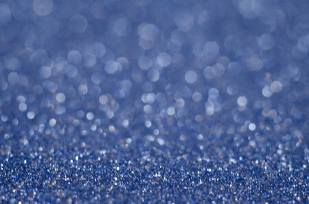 Abstract New Year blue bokeh background with shining defocus sparkles. Blurred glitters shimmering dust macro close up, copy space for text logo. De-focused
