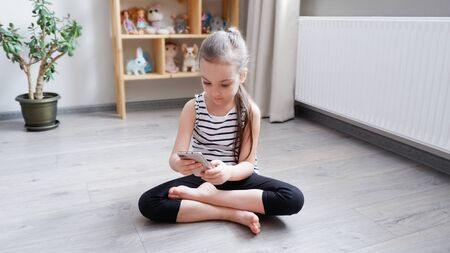 Distance learning. Little girl sitting on a wooden floor with a phone, watching a cartoon or making a video call on a computer Stock Photo