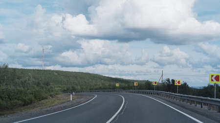 Highway or asphalt road through the forest. An empty roadway. Travel to natural places or reserves. Standard-Bild