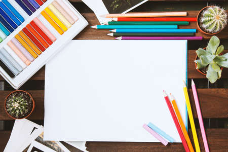 pencils and pastels spread out on a dark table. White blank sheet for text