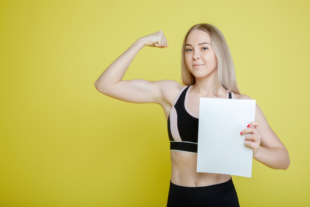 blond female athlete showing biceps on yellow background, holding white sheet Archivio Fotografico