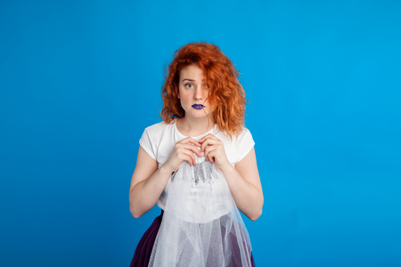 confused red-haired girl in the style of punk. Emotional concept. On brightly blue m background. Place for text.