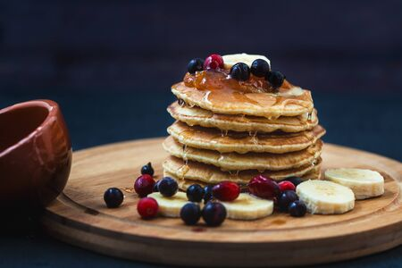 Pancakes with honey, bananas, jam and berrieson a wooden plate Menu , restaurant recipe concept. Served in. Stock Photo