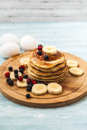 Pancakes with honey, bananas, jam and berrieson a wooden plate on a light background Menu , restaurant recipe concept. Served in Stock Photo
