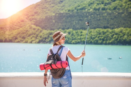 girl traveler makes selfi with an action camera on a mountain lake. She makes a photo for travel blog View from back of the tourist traveler