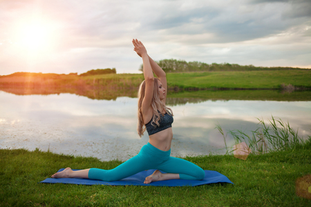 A beautiful blond girl is practicing yoga on the lake at sunset. close-up It supports a healthy lifestyle.