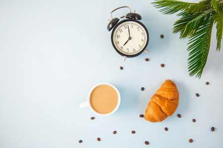 morning coffee in a white cup Croissant on a light background Wake-up with an alarm clock Breakfast cheerfulness, a healthy breakfast freshness Flat lay Copy spase Фото со стока