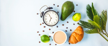 morning breakfast ,coffee in a white cup Croissant Avocado Lime Awakening with an alarm clock Cheerful, healthy breakfast fresh Copy space Top view Фото со стока