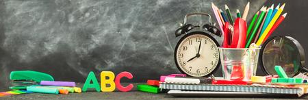 Banner Regreso a la escuela Accesorios para la escuela sobre un fondo oscuro Lápices Letras de plastilina Letras Reloj despertador Tiza Copia espacio.