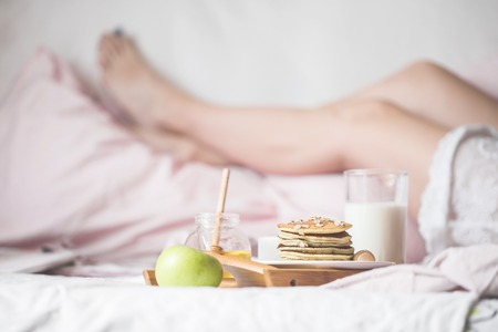 young woman eats a healthy breakfast in bed Stock Photo