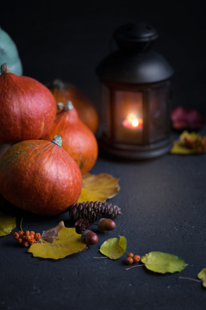 Halloween concept Orange pumpkins, a lantern with candles and foliage on a dark background. Stock Photo