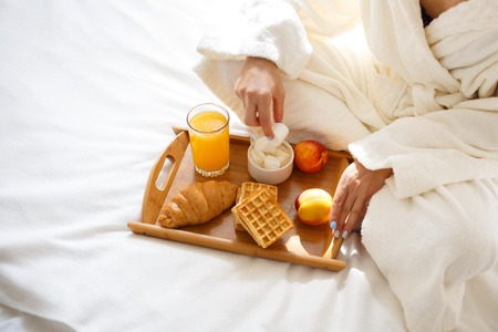 beautiful brunette in a dressing gown and a sweatshirt on her head is having breakfast in bed. Morning concept