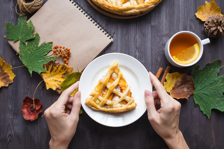 Autumn concept. Female hands hold Pie with peaches Autumn foliage Tea Honey Notepad Coy space Top view