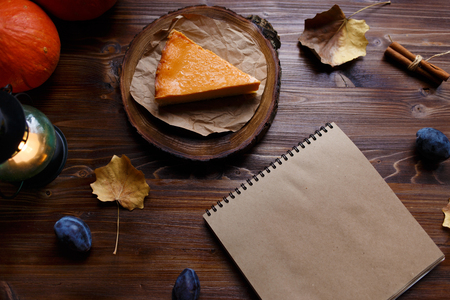Notebook, pumpkin cheesecake, cooked at home, pumpkin, foliage, table lamp, vanilla on a wooden dark table Copy space