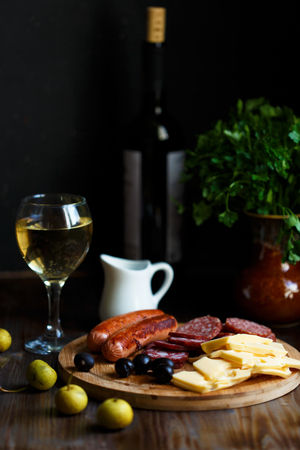 Aperitif table Meat snack, fried sausages, cheese, salami, olives and a glass of wine on a dark table Menu and restaurant concept Close up