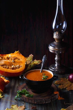 Pumpkin soup puree with greens in a plate on a dark table. On the background of pumpkins Stock Photo