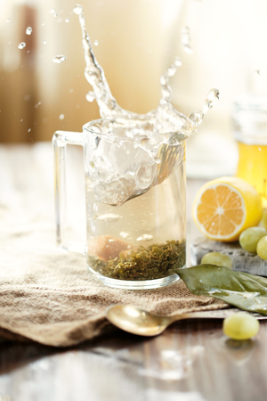 A mug of tea with large splashes, lemon, grapes on the table. Morning concept