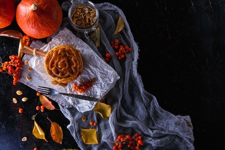 Autumn concept. Pumpkin pancakes with caramel topping, with pumpkins, leaves on a dark background.