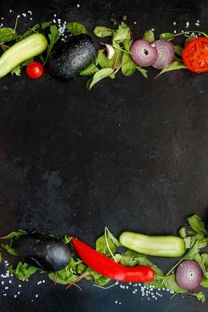 Ingredients for Salad or Veggie Hamburger Fresh Greens, Arugula, Chard, Pepper, Chili, Tomatoes, Cherry, Cucumber, Onion, Fresh Bread on a dark background Copy space Stock Photo