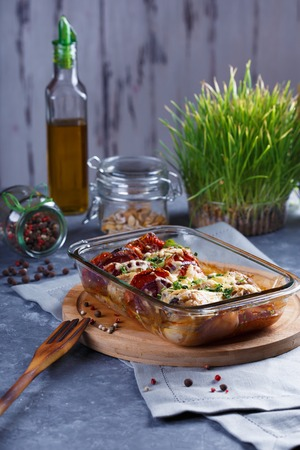 Chicken Casserole of Tomatoes, Onions, Cheese and Spices Menu and Restaurant Concept On Gray Background On the Kitchen Table with Dining Accessories.