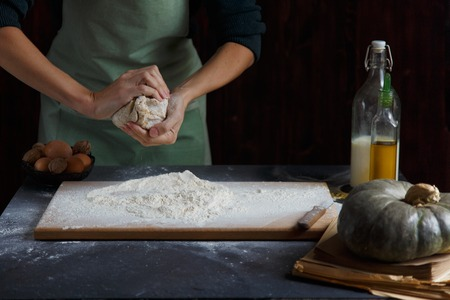 Womens hands knead the dough. Baking ingredients on wooden table Pumpkin Milk Oil Flour Copy space