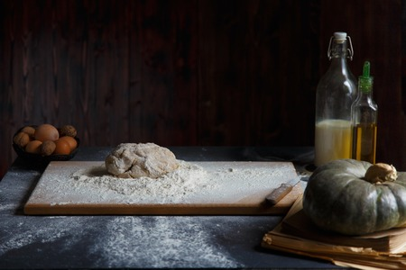 Baking Ingredients Eggs Pumpkin Butter Milk Nuts Flour On A Wooden Table Against A Dark Background Cope space Stockfoto