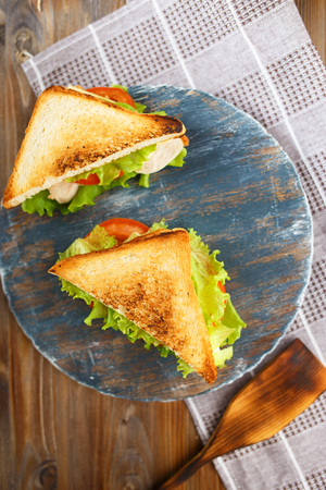 Appetizing sandwich with chicken, tomatoes, lettuce, cheese on a wooden plate on a dark background Copy space Restaurant and menu concept