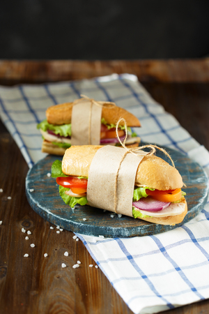 Appetizing sandwich from crispy bread with chicken, onion, tomatoes, lettuce, cheese and spices on a dark wooden background. Restaurant and menu concept. 写真素材