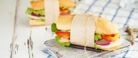 Appetizing sandwich from crispy bread with chicken, onion, tomatoes, lettuce, cheese and spices on a light wooden background. Restaurant and menu concept. Banner