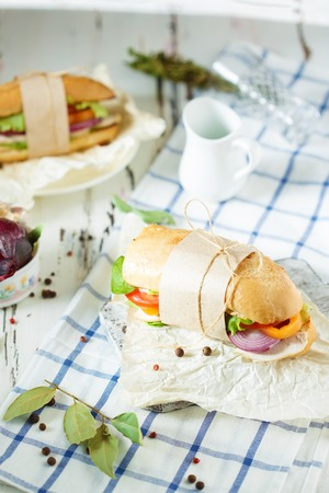 Dining table. Appetizing sandwich from crispy bread with chicken, tomatoes, onion, lettuce, cheese and spices on a light wooden background. Restaurant and menu concept. 写真素材