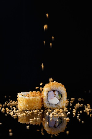 appetizing baked sushi roll with fish sprinkled with bread crumbs on a black background with reflection Menu and restaurant concept Copy space