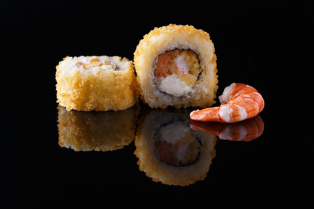 delicious sushi roll with shrimp on a black background with reflection Menu and restaurant concept Copy space