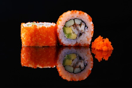Appetizing sushi roll with fish and caviar, on a black background with reflection. Menu and restaurant concept. Copy space