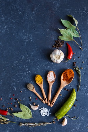 Herbs and spices on black background Food background measuring spoon . spice spoon laurel Copy space