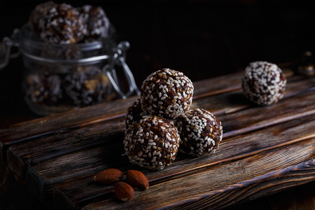 Healthy energy organic vegetarian bites with nuts, dates, honey and sesame on a dark wooden background. Stok Fotoğraf - 113918662