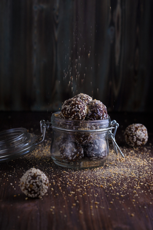 healthy energy granola bites with nuts, dates, honey and sesame in a glass jar on a dark wooden background Copy space Reklamní fotografie