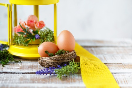 Easter concept. Bright spring flowers with Easter eggs near a yellow decorative lantern Copy space On a light background