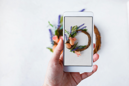 Female hand with phone photographs Easter wreath with bright spring flowers, nest with easter eggs Copy space Light background