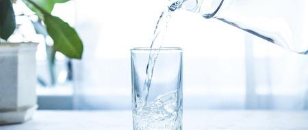 Versare acqua sul vetro sul tavolo bianco Copia spazio Banner
