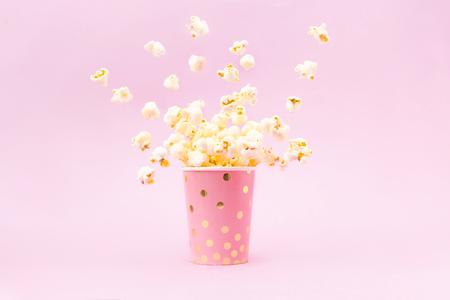 Popcorn volanti in un bicchiere luminoso e su uno sfondo rosa. Copia spazio