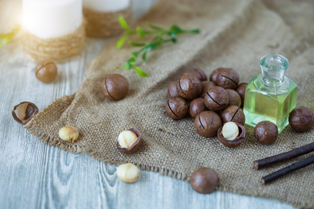 Macadam nuts, walnut oil, on wooden background. Relax, health care, body care Healthy food