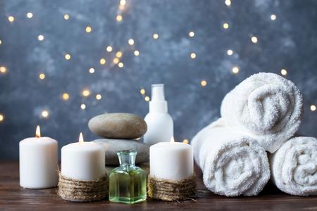 Fondo de spa, tratamientos de belleza y bienestar Toalla de aceite de masaje cosmético y candelabro ardiente, piedras de masaje calientes Foto de archivo