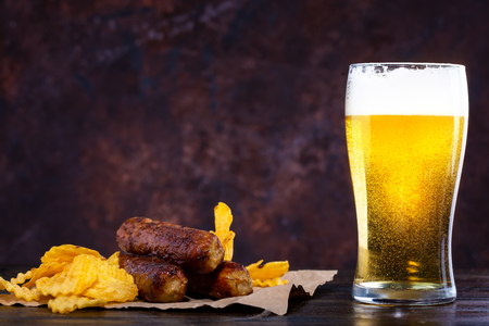 glass of beer with foam, fried sausages and chips on a dark background Copy space