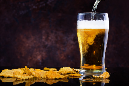 pouring beer into glass and chips on dark wooden background Copy space Stock Photo