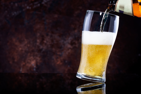 pouring beer into glass on dark wooden background