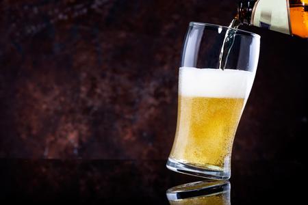 Verter la cerveza en un vaso sobre fondo de madera oscura.