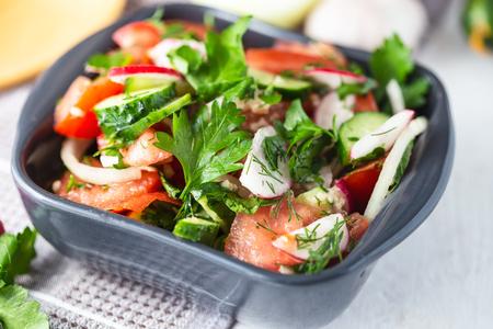 vegetarischer Salat aus Frühlingsgemüse. Tomaten, Gurken, Rettich, Zwiebeln. Diätgericht auf einem hellen Tisch.