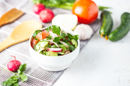 vegetarian salad of spring vegetables. tomatoes, cucumber, radish, onions. Dietary dish on a bright table. Imagens