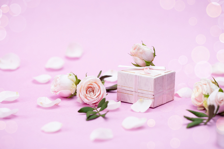 Rosebuds, petals,, gift box on a pink background. Concept for a greeting card. Weddings, Valentines Day, Birthday