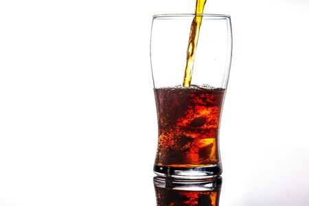 pouring cola into glass with ice on white background Copy space